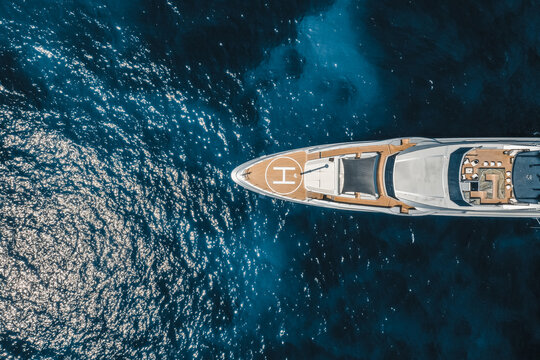 Aerial view of yacht in blue sea with helipad, Saint Tropez, France.