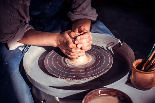 Potter's hands and potter's wheel. Close-up.