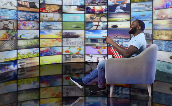 Man has fun watching a film. Concept of entertainment and streaming tv. red background