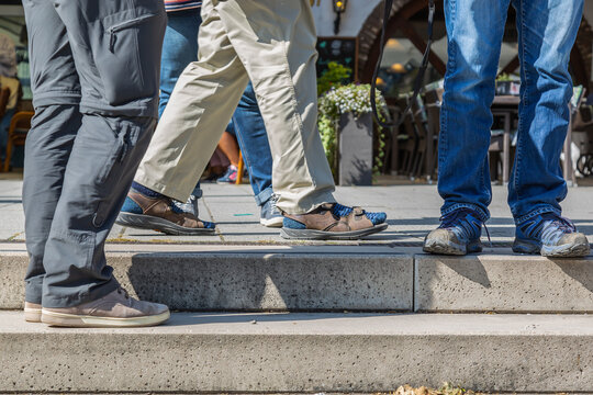 KOBLENZ, GERMANY - Sep 19, 2020: Legs of a group of men standing too close together, no sufficient distance to prevent Corona