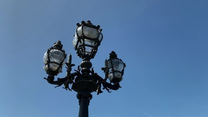 Fotomurales - Footage of traditional street lamp in Paris. It is a sunny summer day. Camera pans right. Sun light effects occur.