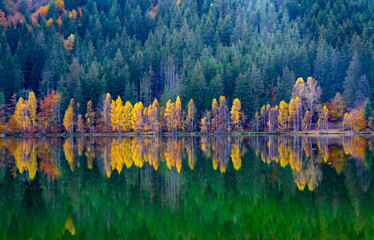 Shot of autumn scenery of Lake Saint Ann in Romania, lush colorful trees reflected in the water