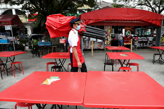 Malaysian former pilot Azrin Mohamad Zawawi prepares to open his food stall in Subang Jaya