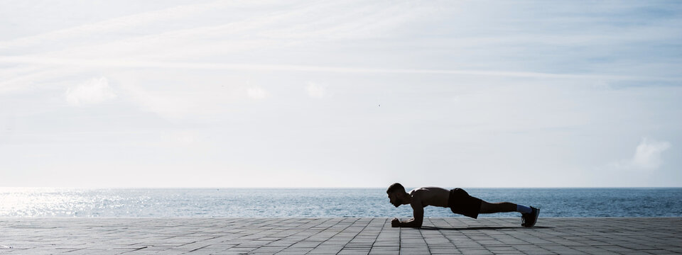 Fit young man doing plank on seafront. Fitness training in morning outdoors. Working out during lockdown outside the gym.