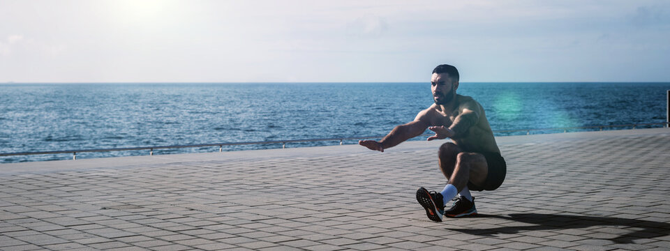 Fit young man doing pistol squats on seafront. Fitness training in morning outdoors. Working out during lockdown outside the gym.