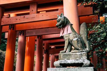 Fox sculpture with red torii gates at Fushimi Inari Taisha Shrine in Kyoto, Japan