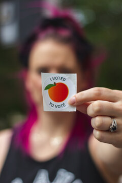 """LAWRENCEVILLE, UNITED STATES - Oct 29, 2020: A Georgia voter displays her """"I Voted"""" sticker after voting in the 2020 Presidential Election"""