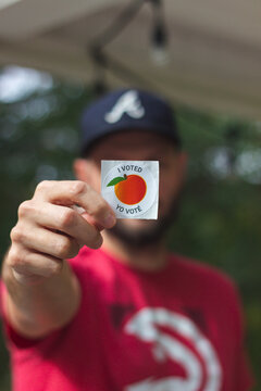 """LAWRENCEVILLE, UNITED STATES - Oct 29, 2020: A Georgia voter holds up his """"I Voted"""" sticker after voting in the 2020 Presidential Election"""
