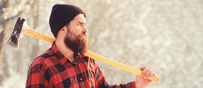 Lumberjack with an ax in his hands. Male holds an ax on a shoulder. Brutal bearded man. Bearded lumberjack. Brutal bearded lumberjack with ax in winter forest. Handsome man, hipster in snowy forest