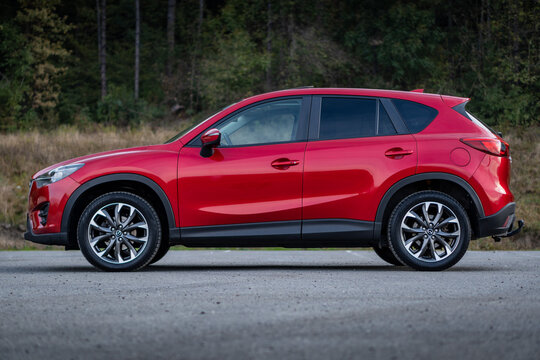 Cluj-Napoca, Cluj/Romania-01.11.2020-Mazda CX-5 in red metallic colour,  AWD, isolated in an empty parking lot, autumn decor, 2016 manufacturing year