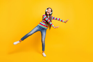 Full length body size photo of laughing girl with headphones smiling dancing balancing isolated on bright yellow color background