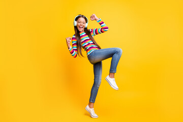 Full length body size photo of careless cheerful girl with earphones dancing gesturing like winner isolated bright yellow color background