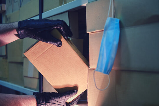 Man hands in black gloves steal a box in a warehouse at night. Loss and theft in a warehouse during a lockdown due to coronavirus