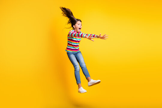 Full length body size photo of kicked up schoolgirl in windy weather isolated on vivid yellow color background