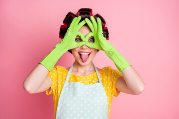 Playful girl make okay sign binoculars show tongue out wear green latex gloves isolated over pastel...