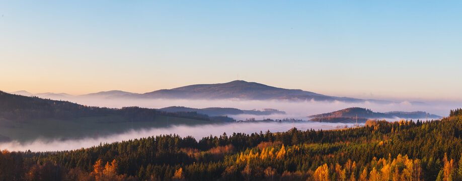 misty landscape at sunset, mountains rising from clouds of fog in the background, clear sky - mountain Klet, Czech republic