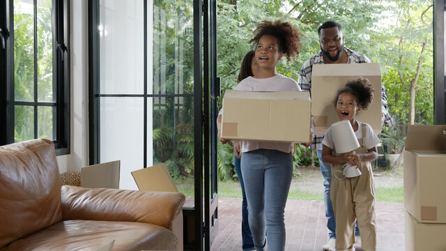 Candid african american family, parents and little girl holding carton box walk into new house move in day,relocate in existing second hand home. Loan mortgage finance in real estate property concept.