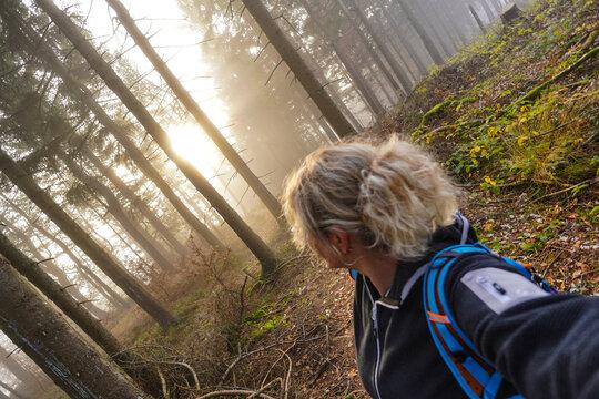 Frau im Wald beim Wandern Sonnenstrahlen  im Herbst
