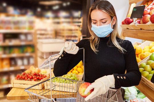 Frau mit Mundschutz beim Einkaufen im Supermarkt