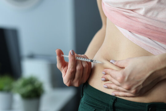 Woman making skin fold on stomach and injecting medicine from syringe at home. Continuous administration of insulin in treatment of type 2 diabetes mellitus concept