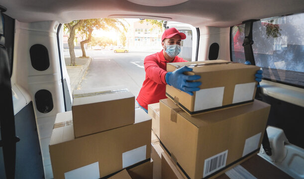 Delivery man picking box from van with face mask - Shipment service during coronavirus outbreak - Focus on face