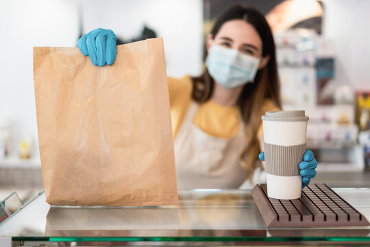 Young worker woman delivering takeaway food with face mask - Focus on coffee cup