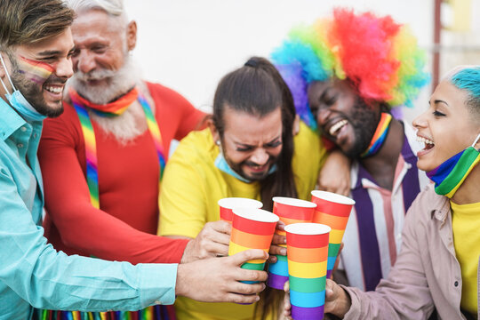 Happy multiracial group of friends having fun at LGBT gay pride event cheering with rainbow drinks - Focus on close-up glasses
