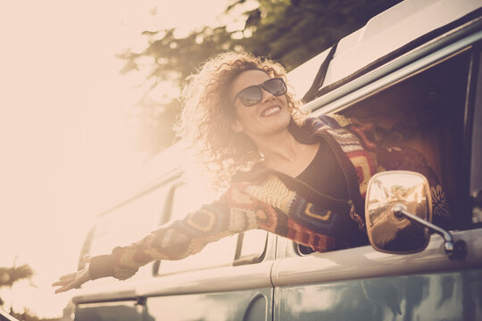 Travel and happiness concept lifestyle with cheerful happy and joyful beautiful lady outside the window of the van vehicle and wind in the hair - people enjoy the road trip in summer style
