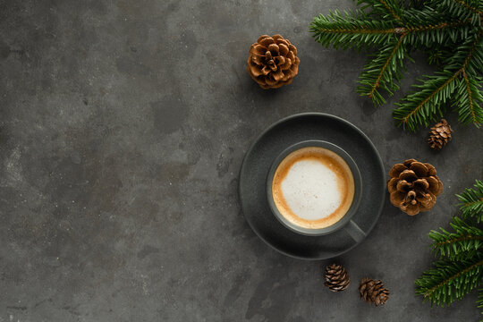 A photo of cappuccino with chocolate donuts and christmas decoration.  Grey cups on the grey table and a grey wall. Place for text