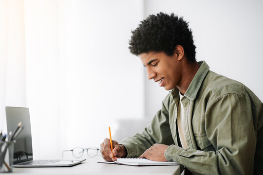 Web-based training concept. Black male student writing in notebook in front of laptop at home, empty space