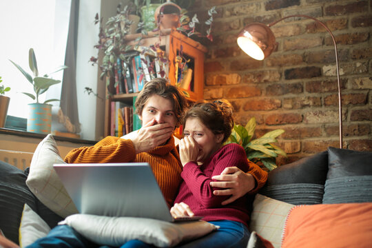Young man and woman lying on the sofa, watching an horror movie on the laptop