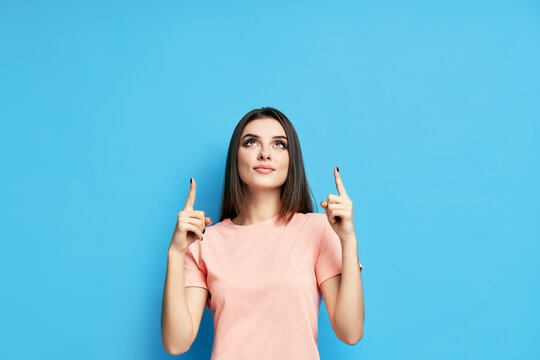 Pretty happy woman pointing her fingers up showing empty copy space