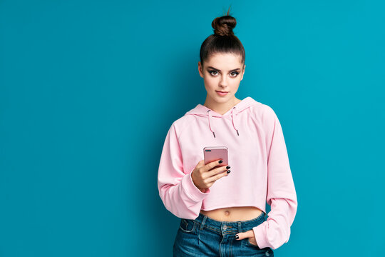 Pretty millennial hipster girl holding mobile phone and looking to camera in blue studio background