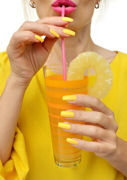 Young woman drinking pineapple juice with joy. Trendy manicure with yellow nail polish on a long form.