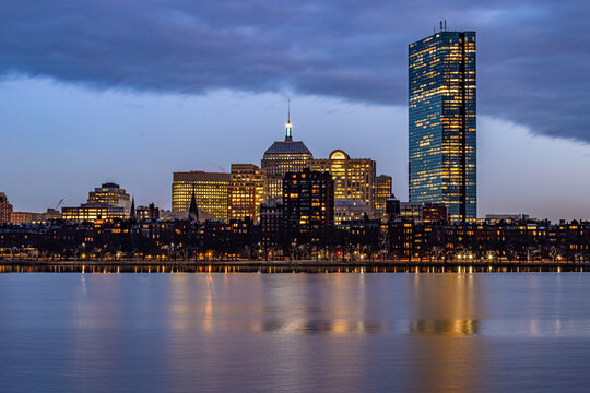 Blue hour cityscape buildings reflecting in water.