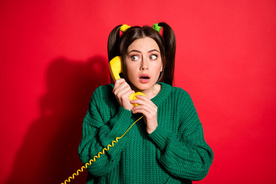 Photo of young scared worried shocked girl talk telephone look copyspace isolated on red color background