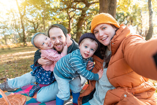 Happy family taking a selfie together on a sunny autumn day - Mother and father holding their daughter and son and having fun all together in a cute group hug
