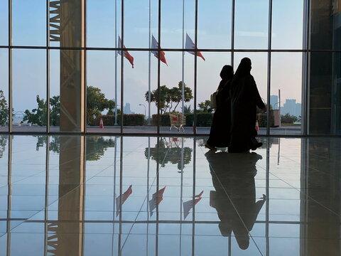 Women walk in front of Bahraini flags flying at half-mast following the death of Bahrain's Prime Minister, Sheikh Khalifa bin Salman al-Khalifa, in Seef Mall in Muharraq
