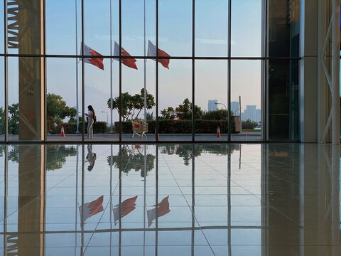 A woman checks her smart phone in front of Bahraini flags flying at half-mast following the death of Bahrain's Prime Minister, Sheikh Khalifa bin Salman al-Khalifa, in Seef Mall in Muharraq