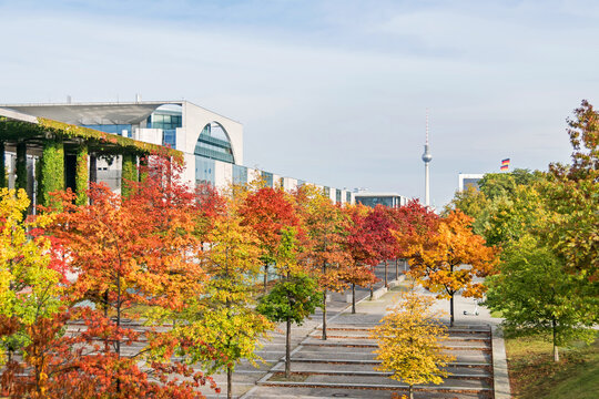 Paul Loebe Allee lined with autumn coloured trees, Bundeskanzleramt and the television tower in Berlin, Germany