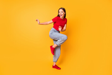 Full length photo of dancing lady at students party wear red crop top jeans shoes isolated yellow color background
