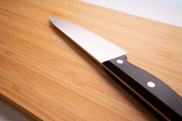 Knife on the background of a board for cutting a wooden bamboo