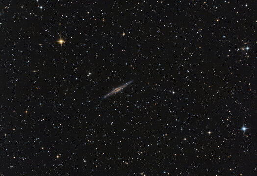 """Close up to the NGC 891 galaxy in Andromeda constellation, taken with my telescope, the red bright star is called """"HD 14771"""" and the blue one at the bottom right, it is called """"V* V436""""."""