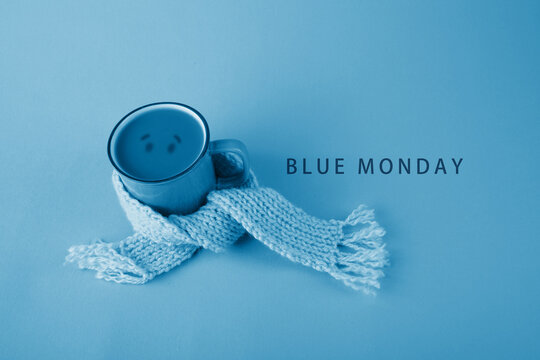 Blue cup with scarfcoffee on blue background. Blue monday concept