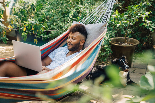 Man working from home on laptop computer while relaxing in hammock in the back yard