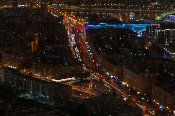 Aerial drone view on Moscow city street with fast moving cars traffic and lights trail. Warm illumination at night. Rush hour, urban, transportation and city life concept Fotomurales
