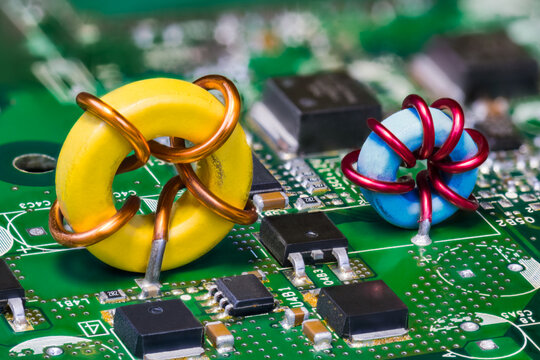 Two toroid inductors and electronic transistors on green circuit board. Beautiful yellow or blue induction coil on PCB in embedded voltage converter of computer mainboard detail. Semiconductors. Tech.