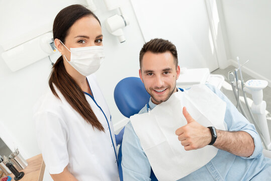 Young doctor dentist and patient showing thumb up