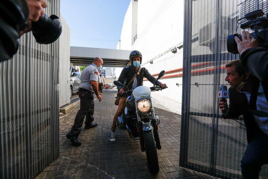 Personal physician of Argentine soccer great Diego Maradona, Dr. Leopoldo Luque, rides a motorcycle as he prepares to speak to the media outside the clinic where Maradona underwent brain surgery, in Olivos