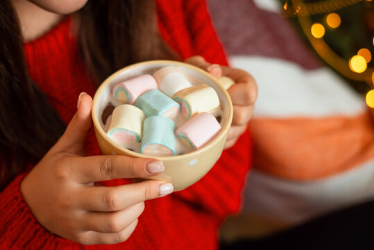 Close-up shot of cup with cocoa and marshmello in hands of young brunette woman in red knitted sweater. Cozy festive atmosphere, holidays at home concept.